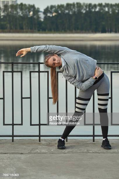 Young female athlete exercising on footpath against lake