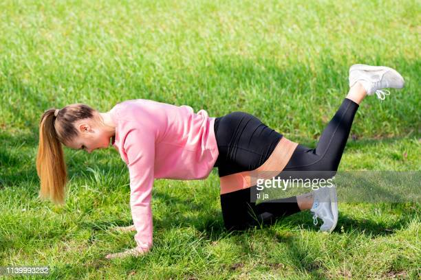 young female athlete exercising outdoors in nature - elastic bandage stock photos and pictures
