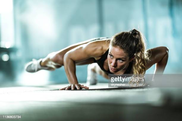 young female athlete exercising push-ups with in a gym. - atleta imagens e fotografias de stock