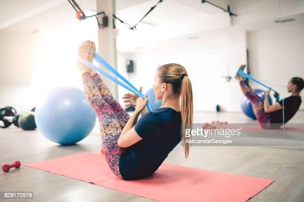 junge sportlerin mit gummiband im fitness-studio trainieren - gummihose stock-fotos und bilder