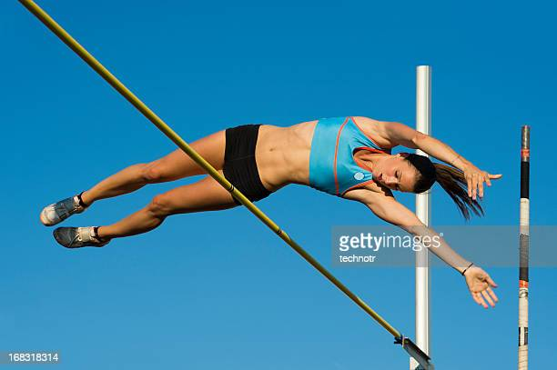 Junge weibliche Athleten springen über die lath