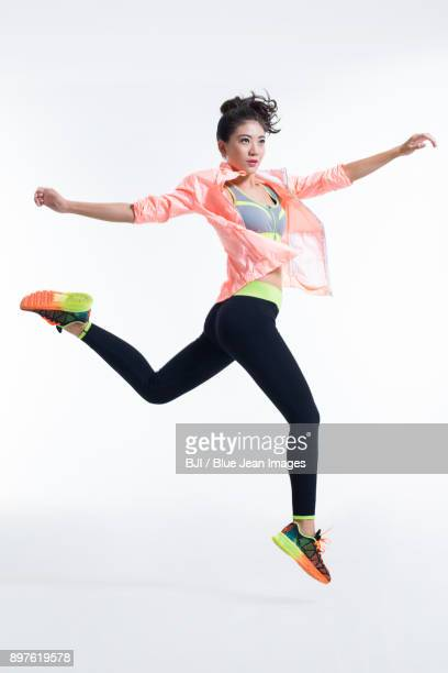 young female athlete jumping - asian female bodybuilder stock photos and pictures
