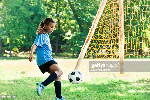 Young female athlete kicks soccer ball into goal