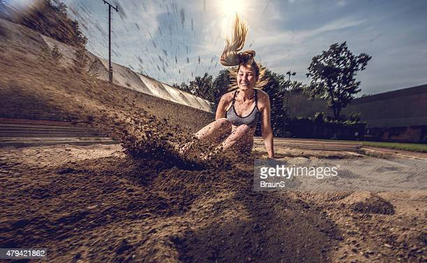 Young female athlete landing in sand after a long jump.