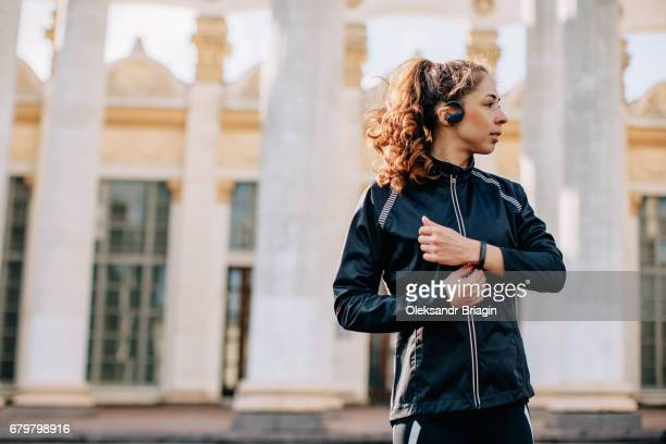 Young female athlete listening portable music player outdoors