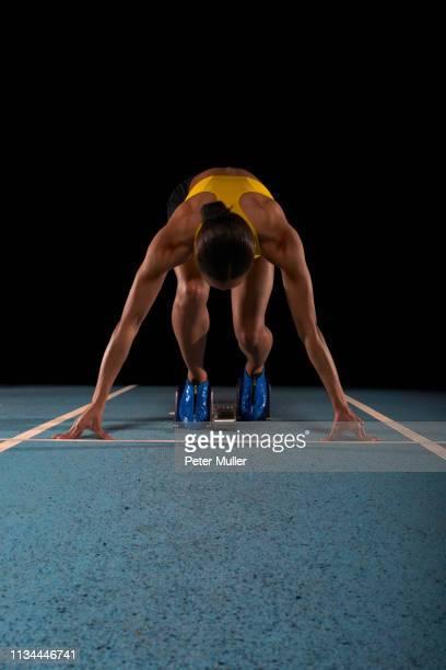 young female athlete on starting blocks - 陸上競技大会 ストックフォトと画像