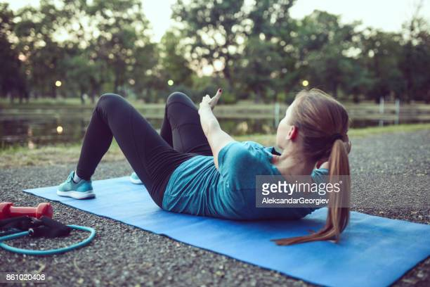 young female athlete performs abs crunches in city park - sit ups stock photos and pictures
