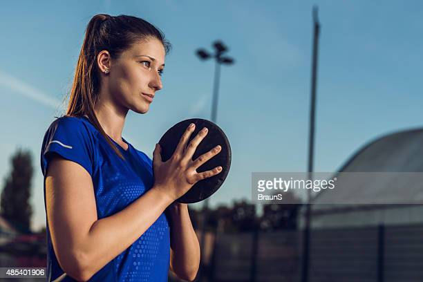 Young female athlete preparing to throw a discus.