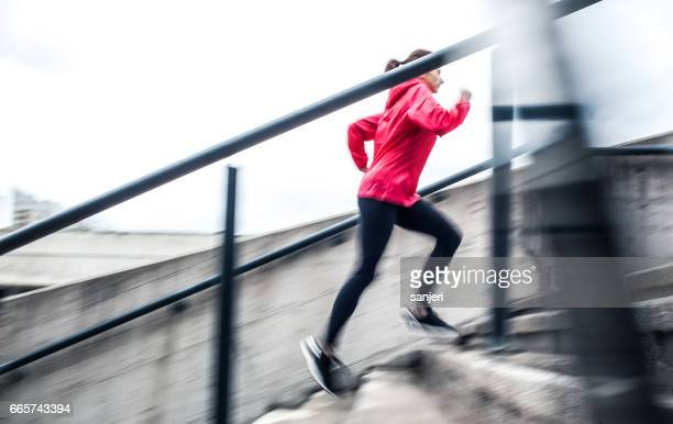Young Female Athlete Running up The Staircase
