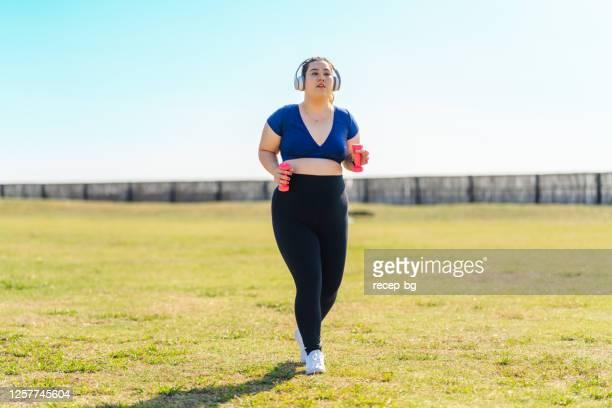 草の上に手の重みを保持しながら走っている若い女性アスリート - ポジティブなボディイメージ ストックフォトと画像