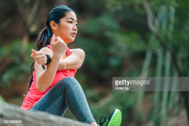 young female athlete stretching her arms and legs and warming up for sports training - warming up stock pictures, royalty-free photos & images