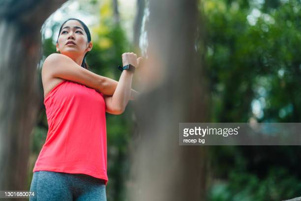 young female athlete stretching her arms and warming up for sports training - waist up stock pictures, royalty-free photos & images