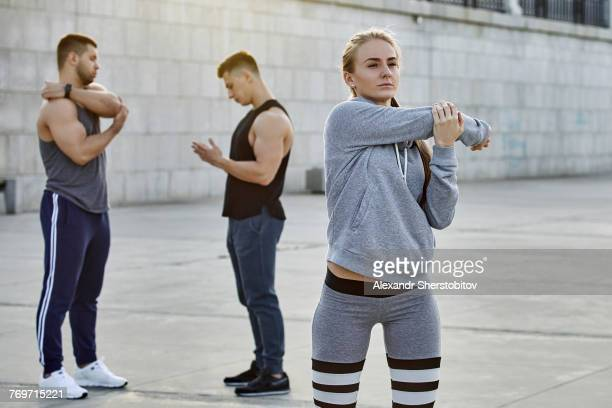 Young female athlete stretching with friends standing in background on footpath