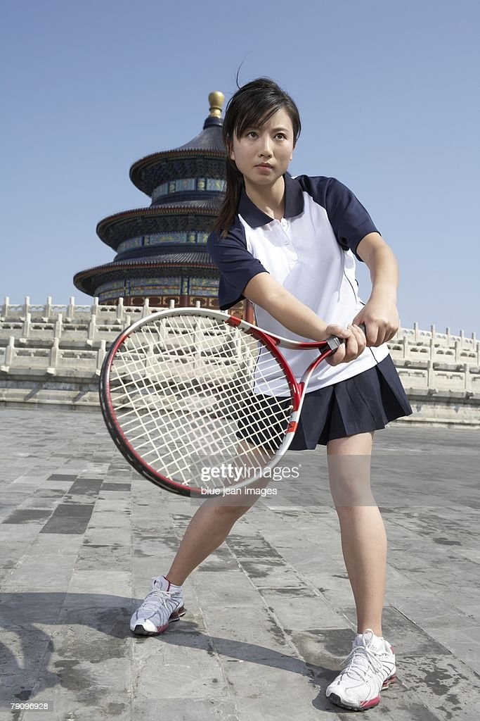 A Young Female Athlete Swings A Tennis Racquet With Beijings Temple Of Heaven In The Background