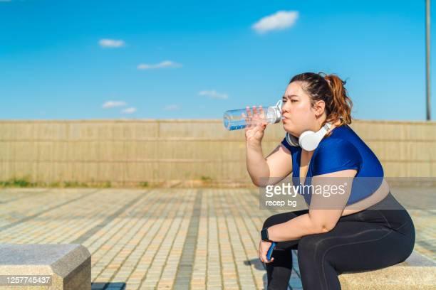 ビーチでスポーツトレーニングを休む若い女性アスリート - 体への関心 ストックフォトと画像