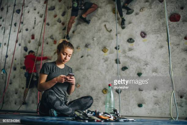 young female athlete using cell phone in bouldering gym. - outdoor pursuit stock pictures, royalty-free photos & images