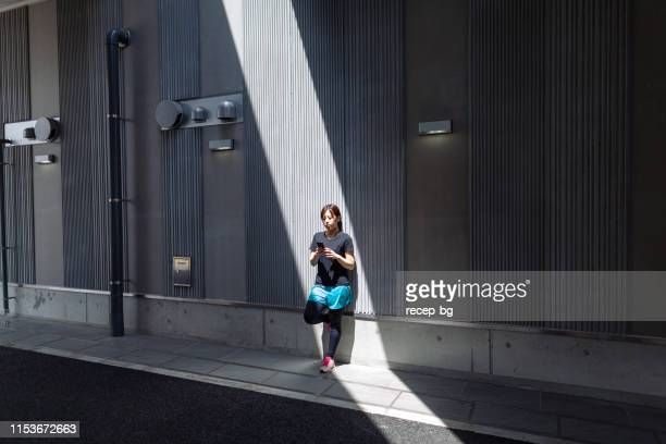 young female athlete using smart phone in city - sunbeam stock pictures, royalty-free photos & images