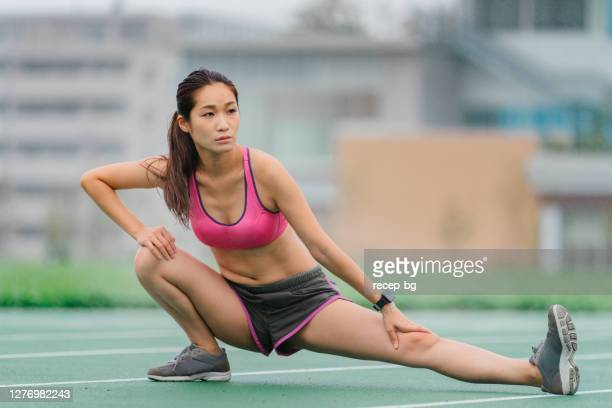 young female athlete warming up before sports training - all weather running track stock pictures, royalty-free photos & images