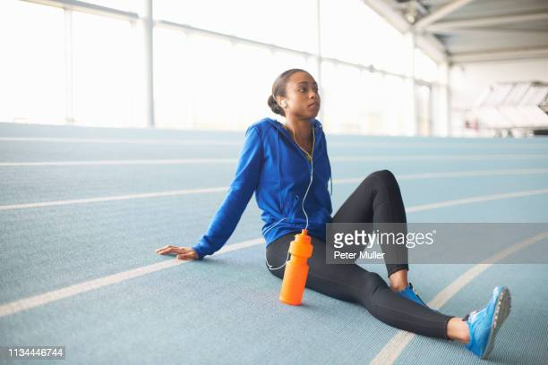 young female athlete wearing earphones resting - sport stock pictures, royalty-free photos & images