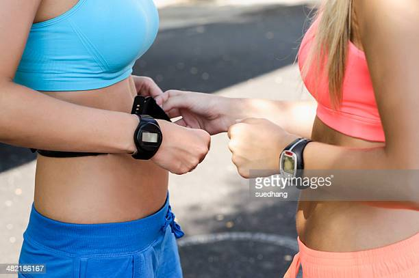 Young female athletes checking heart rate monitors