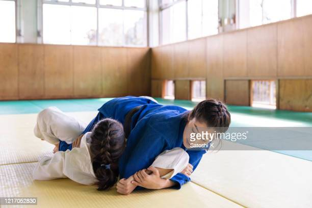young female athletes playing judo in dojo - judo stock pictures, royalty-free photos & images