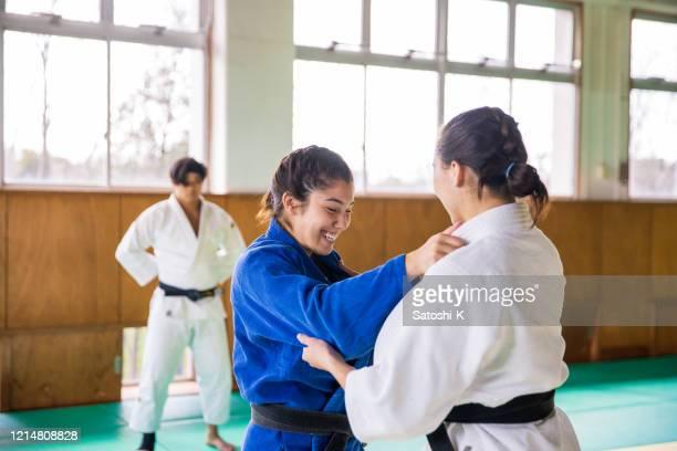 jeunes athlètes féminines pratiquant le judo avec le sourire - judo photos et images de collection