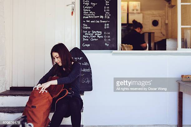 A young female backpacker organising belonging and seating on bench in an outdoor cafe