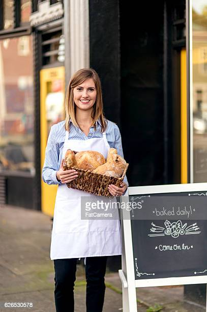 Young female baker holding basket of goods outside downtown store