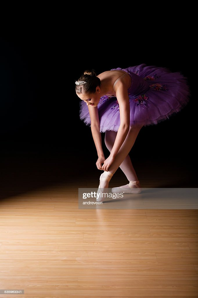 Young female ballerina adjusting her shoes : Stock Photo
