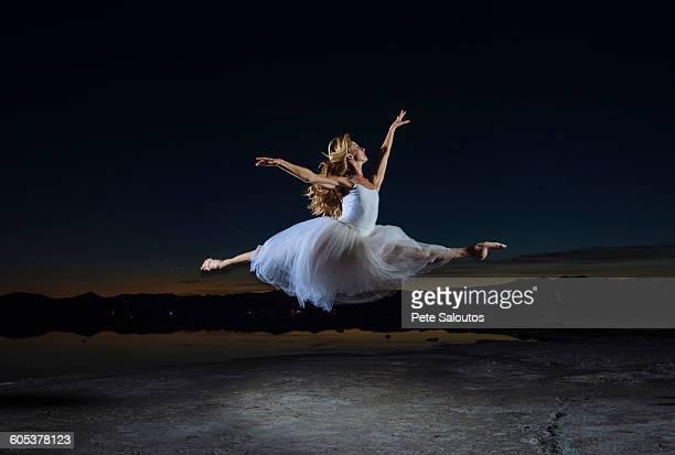 Young female ballet dancer leaping over Bonneville Salt Flats at night, Utah, USA