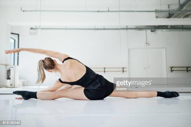 Young female ballet dancer practicing splits
