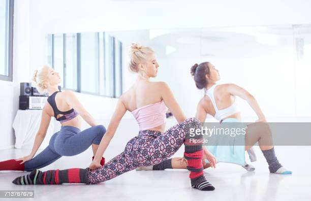 Young female ballet dancers practicing in dance studio, dancing with legs outstretched