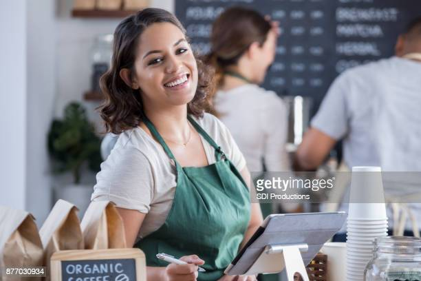 Young female barista smiles for camera at checkout counter