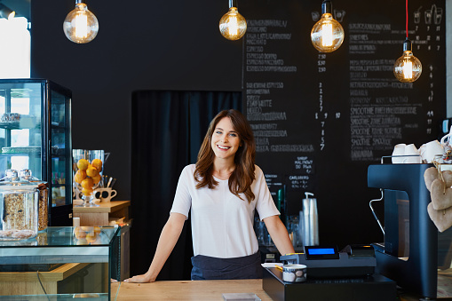 Young female barista standing behind the bar in cafe smiling 964217064