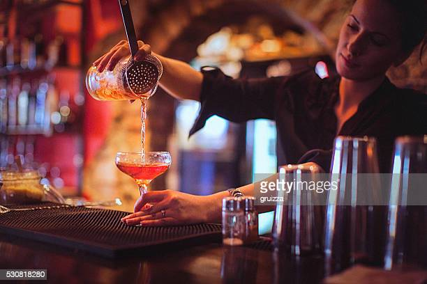 jeune femme barman servant des cocktails dans un bar à cocktails - comptoir de bar photos et images de collection