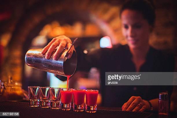 Jeune femme Barman servant des cocktails dans un bar à cocktails