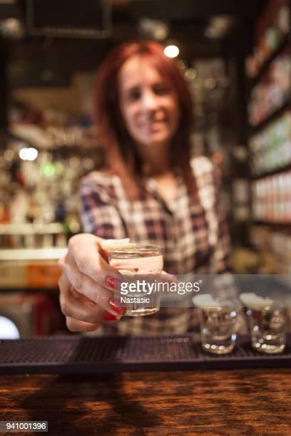 Young female bartender serving shots