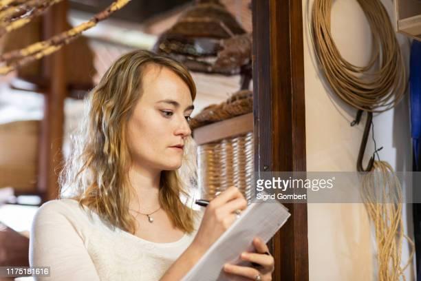 young female basket maker making notes in workshop - sigrid gombert stock-fotos und bilder