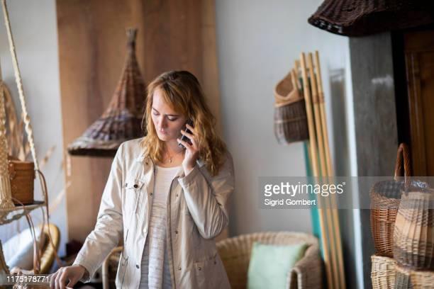 young female basket maker making smartphone call in workshop - sigrid gombert stockfoto's en -beelden