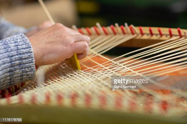 young female basket maker weaving in workshop, close up of hands - sigrid gombert photos et images de collection