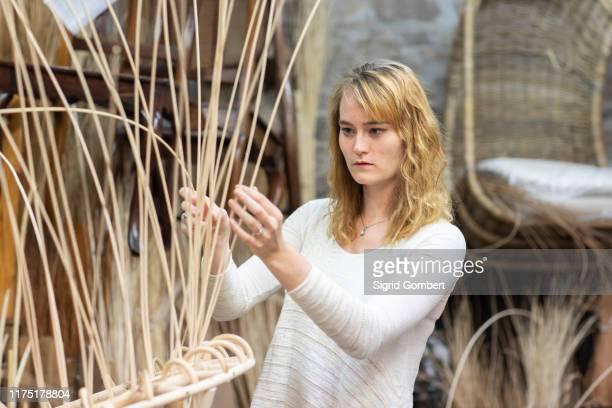 young female basket maker weaving in workshop - sigrid gombert 個照片及圖片檔