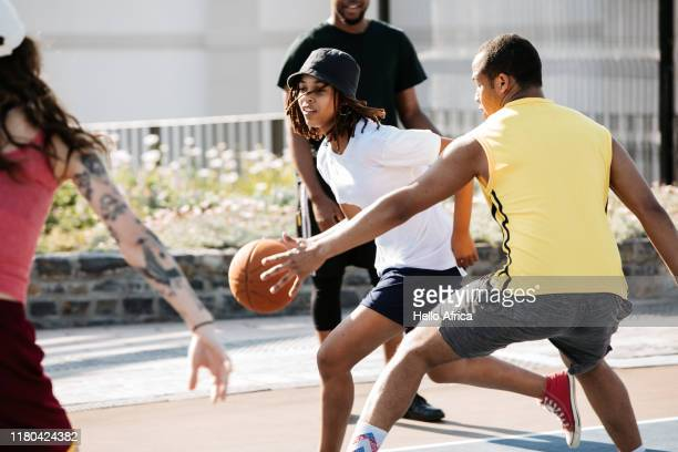 Young female basketball player running past an opponent intent on blocking her