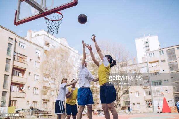 Junge weibliche Basketball-Spieler spielen Basketball auf dem Platz