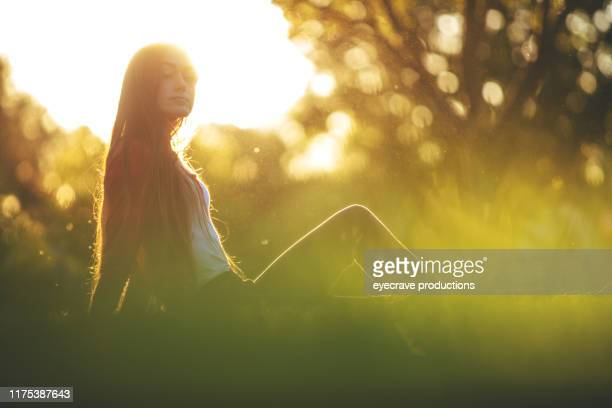 young female beautiful generation y millennial woman with long brown hair in a lush green treed park setting in the summer during sunset hours in grand junction colorado - golden hour stock pictures, royalty-free photos & images