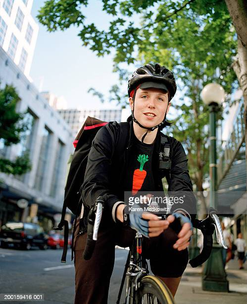 young female bicycle messenger on urban street, portrait - bicycle messenger stock pictures, royalty-free photos & images