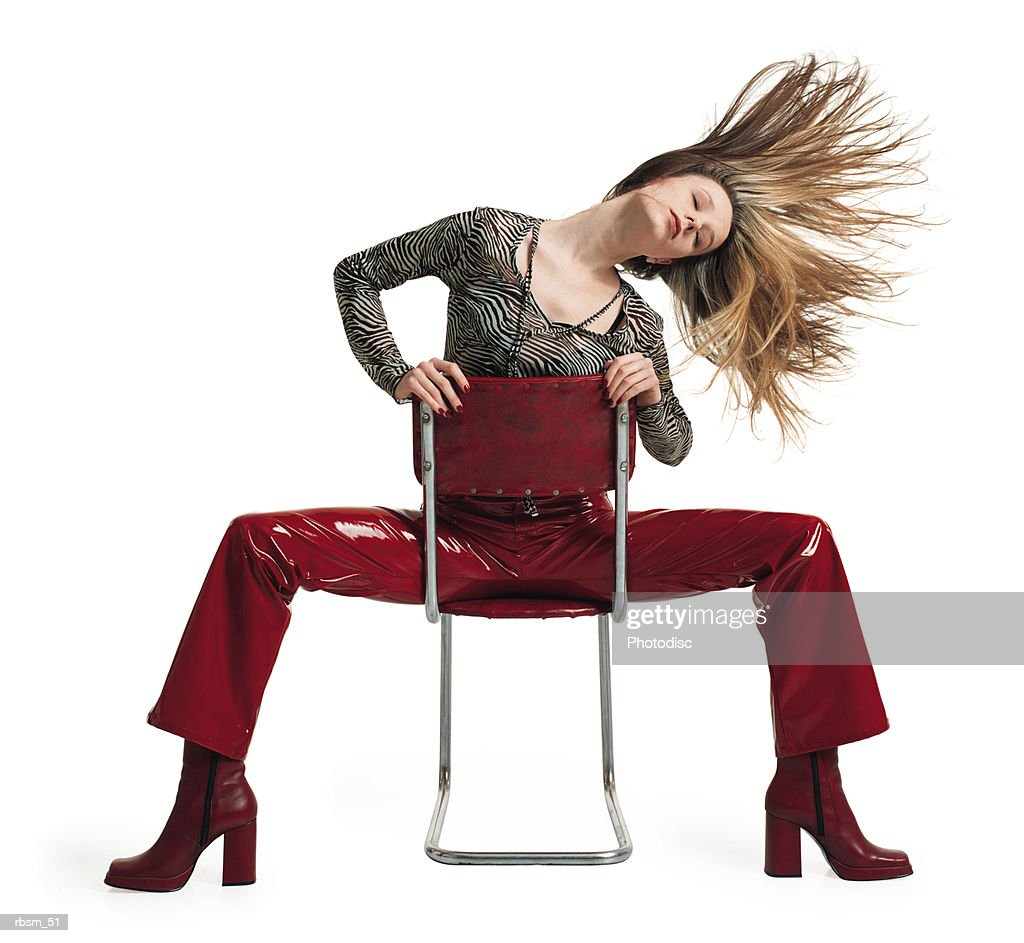 young female blonde hair in red pants zebra print blouse sits backwards on a chair tosses her hair : Foto de stock