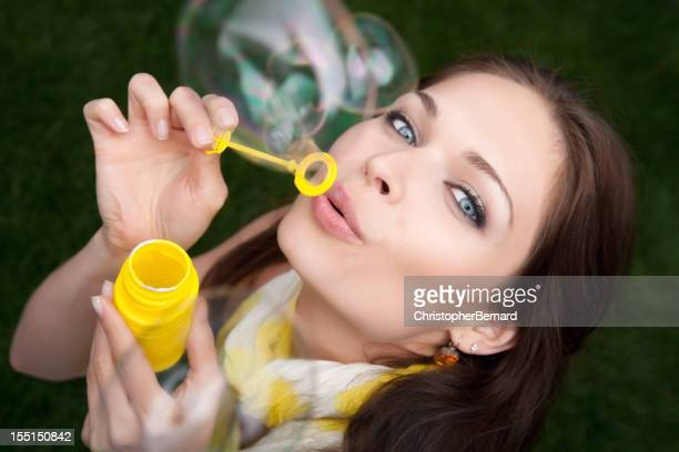 Junge weibliche blowing bubbles