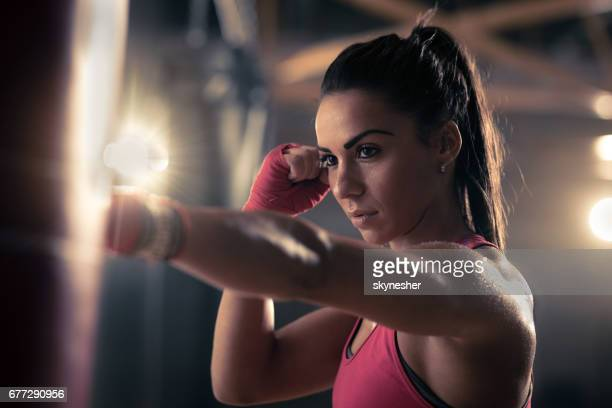 Young female boxer punching a bag during kickboxing training in a gym.