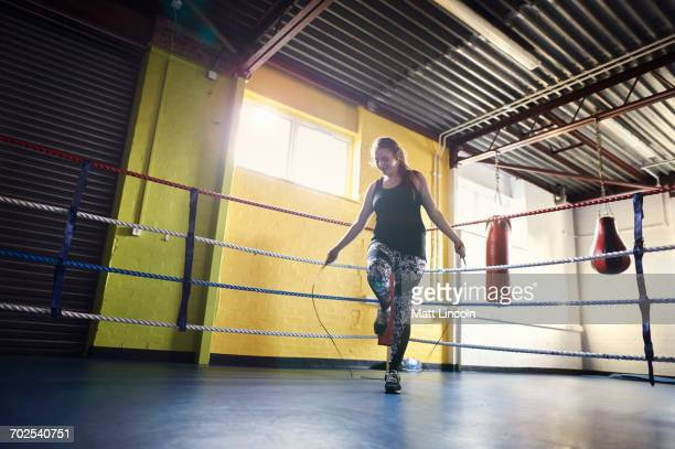 Young female boxer skipping in boxing ring