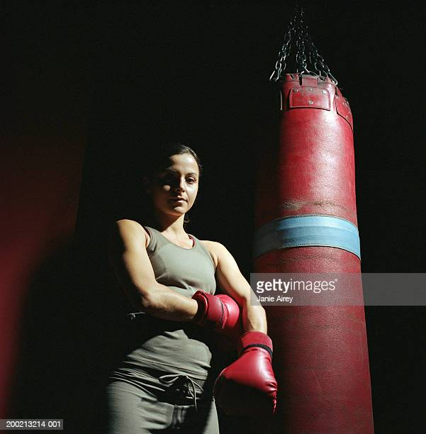 Young female boxer standing by punch bag, portrait, low angle view
